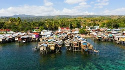Fishing village with wooden houses on stilts in the sea. Village of fishermen with houses on the water, with fishing boats. Zamboanga city, Philippines, Mindanao.