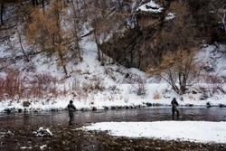 Fishing with artificial flies in the cold waters of winter.  Warm clothing and a passion for the sport is necessary in such frigid conditions.