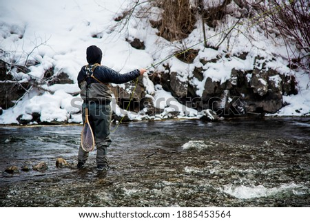 Fishing with artificial flies in the cold waters of winter.  Warm clothing and a passion for the sport is necessary in such frigid conditions. Foto stock ©