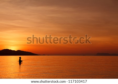 Fishing with spinning on tropical beach at sunset, fisherman silhouette in water