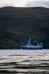 Fishingboat at sea in front of Mountains, Scotland
