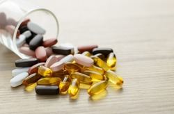 Fishoil capsules and Multivitamin supplements out of the small glass on the wooden table with copy space.Selective focus.