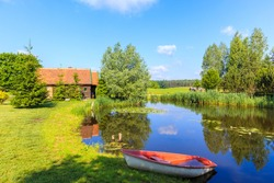 Fishong boat on shore of small pond and old traditional rural house in Galkowo village near Krutynia river, Masurian Lakes, Poland