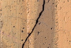 Fissure and crack on a concrete wall. Paint color - Mongoose, Tumbleweed, Hue Brown.