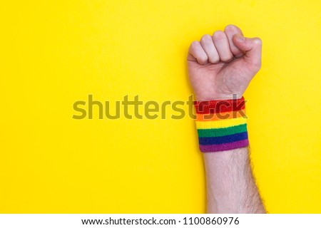 Fist hand with gay pride rainbow flag wristband on a yellow background