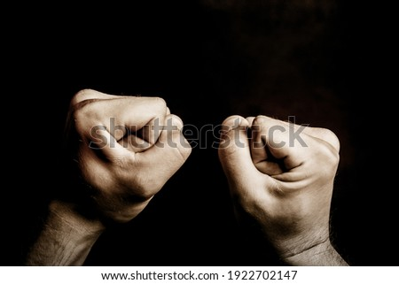Fist isolated on black. Agression background. Artistic light male hands point of view. Fighting empty copy space background. Symbol of power. Dark bully background. Stock photo ©