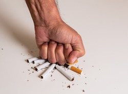 Fist of a man hitting a pile of broken cigarettes on a white table, as a sign of disapproval and rejection of tobacco. May 31, international day without tobacco.
