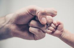 Fist of Dad and Newborn Baby