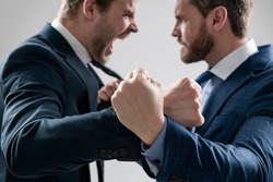 fist of punching disagreed men business partners or colleague disputing and fighting aggressive and angry while conflict, selective focus, corporate battle.