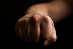 Fist on a black background, a punch in the face