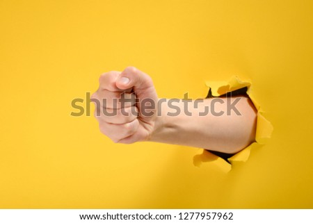 Fist punching through yellow paper background. Threat, fight and combat sports. Push through the wall.