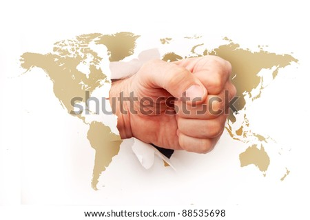 Fist ripping the paper with the world map printed on it.