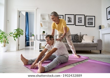 Fit active retired middle aged wife helping senior husband doing stretching exercise at home. Happy healthy older senior 60s couple enjoying fitness sport training workout together in apartment. Stock foto ©