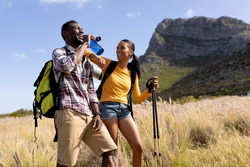 Fit afrcan american couple wearing backpacks nordic walking with poles drinking water in mountain countryside. healthy lifestyle, exercising in nature.