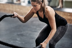 Fit and focused young blonde woman in sportswear working out with ropes during an exercise session in a gym