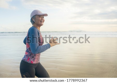 fit and happy middle aged woman running on the beach - 40s or 50s attractive mature lady with grey hair doing jogging workout enjoying fitness and healthy lifestyle at beautiful sea landscape