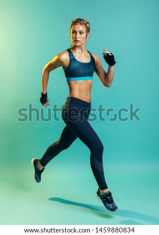 Fit and healthy woman running. Female runner sprinting on blue background.