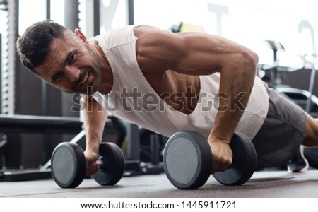 Fit and muscular man doing horizontal push-ups with dumbbells in gym.