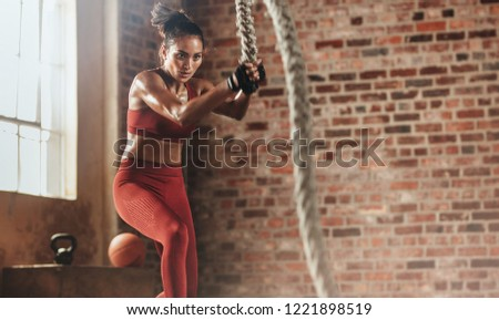 Fit and muscular woman exercising with battling ropes at fitness studio. Female athlete doing battle rope workout at gym. #1221898519