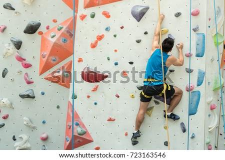 fit asian man rock climbing...