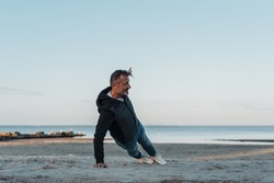 Fit athletic man working out on a sandy tropical beach at sunset doing full body stretches in a low angle view across the sand with ocean backdrop