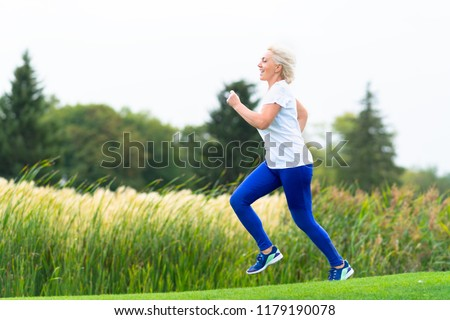 Fit athletic mature woman running alongside reeds on the shore of a lake in a park in a health and fitness concept #1179190078