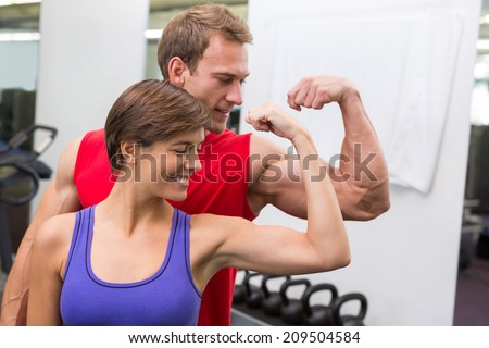 Fit attractive couple flexing their biceps at the gym