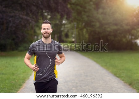 Fit bearded young man jogging through a park listening to music on his mobile phone, upper body approaching the camera with copy space