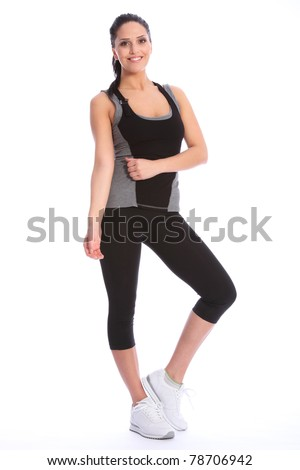 Fit beautiful and young athletic woman standing in a relaxed pose, big smile and wearing a grey and black sports outfit with white trainers.