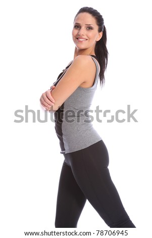 Fit beautiful and young athletic woman standing in a relaxed pose with arms folded, big smile and wearing a grey and black sports outfit.