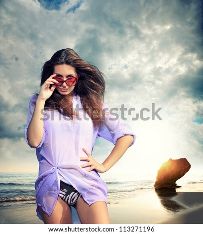 Fit beautiful woman in tropical beach dramatic cloudscape on background