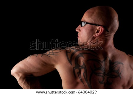 Fit Bodybuilder With Tattoo and Sunglasses On Black Isolated Background
