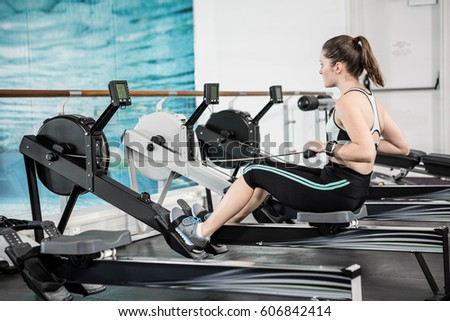 Fit brunette on drawing machine at the gym images and stock photos