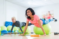 Fit Caucasian female athletes in sportswear doing Pilates exercises with fitness ball in sports club.
