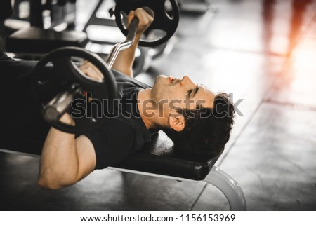 Fit caucasian handsome young man and big muscle in sportswear. Young man holding dumbbell during an exercise class in a gym. Healthy sports lifestyle, Fitness concept. with copy space for your text. #1156153969
