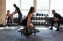 fit caucasian young woman lifting barbells, working out in gym with other people, wearing sportswear, concentrated on exercises
