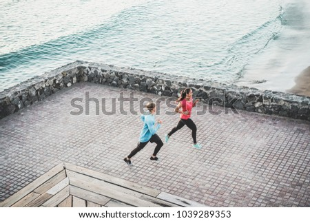 Fit couple doing jogging next to the ocean - Joggers running outdoor - Fitness, wellness, training, sport, workout, healthy lifestyle concept - Focus on bodies #1039289353