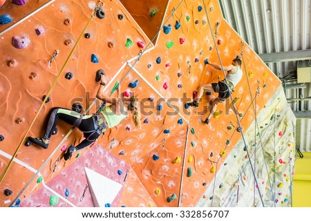 Fit couple rock climbing indoors at the gym #332856707