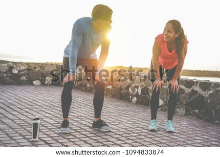 Fit couple taking a rest after fast running workout - Joggers training outdoor at sunset together - Main focus on girl face - Fitness, sport, wellness, workout, gym and healthy lifestyle concept