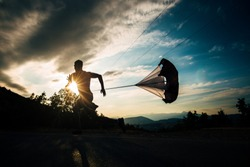 Fit cross fit man sprint in mountain path while carrying parachute for resistance training on the mountain with a parachute tied behind him. Fitness man running hard with a drag parachute