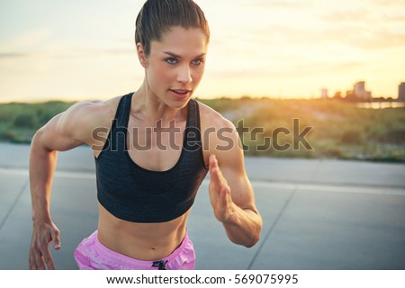 Fit determined young woman runner training at sunrise on a rural road sprinting towards the camera with a focused expression