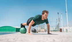 Fit exercises man strength training core doing balance push-ups workout at outdoor gym balancing on stability medicine ball with legs. Bodyweight pushups exercises. Push-up variation.