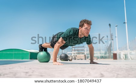 Photo of  Fit exercises man strength training core doing balance push-ups workout at outdoor gym balancing on stability medicine ball with legs. Bodyweight pushups exercises. Push-up variation.