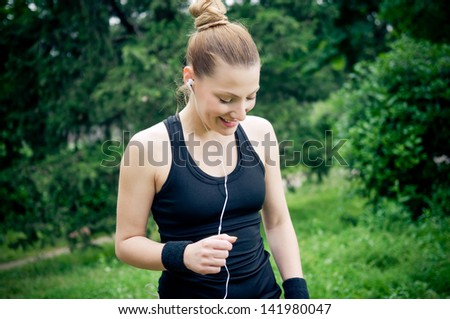 Fit female athlete enjoying music
