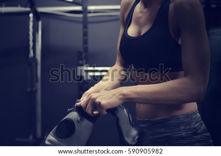 Fit female putting on boxing gloves for workout at the gym.