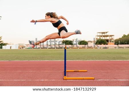 Fit female teenager athlete hurdler running jumping over hurdles Сток-фото ©