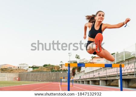 Fit female teenager athlete hurdler running jumping over hurdles Foto stock ©