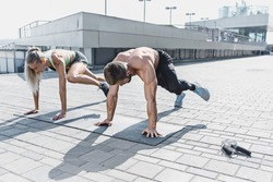 Fit fitness woman and man doing fitness exercises outdoor at city background. Couple doing hamstring leg exercise and stretches. Female amd male sports models exercising in summer at morning.