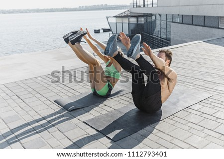 Fit fitness woman and man doing fitness exercises outdoor at city background. the best abdominal muscle press in the world. Female and male sports models exercising in summer at morning. #1112793401