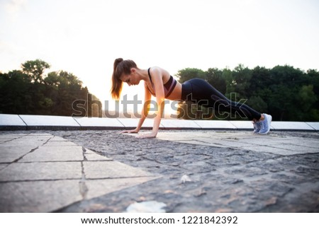 Fit girl doing plank exercise outdoor in the park warm summer day. Concept of endurance and motivation #1221842392